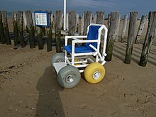 A chair with four wide, balloon-style wheels is in front of a fence at the beach